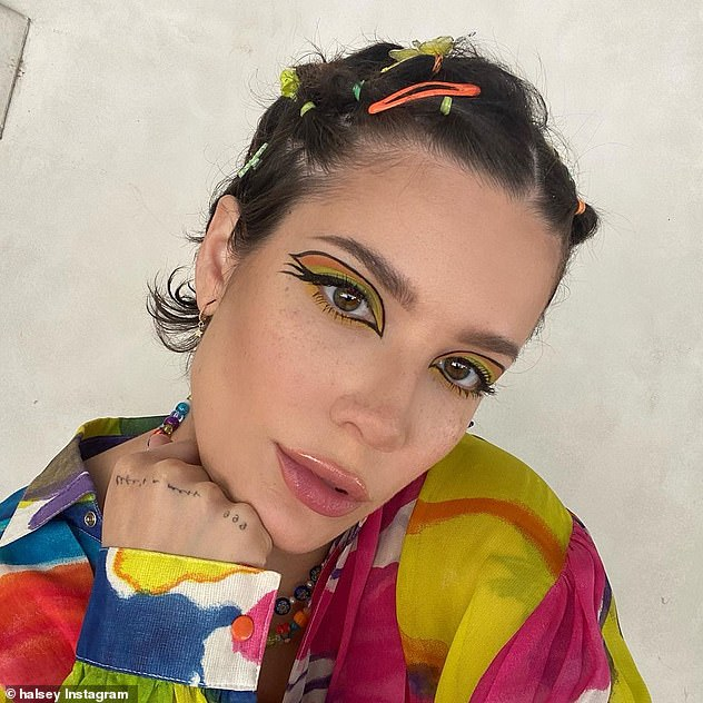 Standing out:The Without Me singer shared a selfie on her Instagram page ahead of the event in which she was sporting dramatic, colorful eye makeup as well as a wild print shirt dress with her hair clipped with several multi-colored barrettes