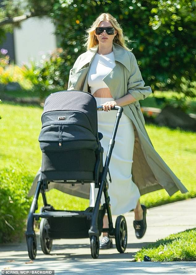 Mommy and me: Elsa Hosk flashed a little skin in a calf-length white dress with cutout panel at the waist as she took baby daughter Tuulikki out for a walk on Sunday in Pasadena, California