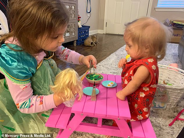 Emily said her protective older daughter Samantha, who is four, is a 'rock' and knows Abigail, well, needs extra help (pictured playing together)