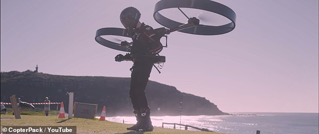About three feet in diameter, the rotors connect to a backpack with a battery packs and a pair of flat armrests with hand controls