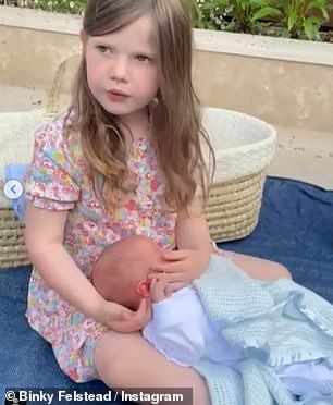 Family: In a second clip, India cradled her baby sibling in her arms as she told Binky and Max that she 'didn't want him to ever go'