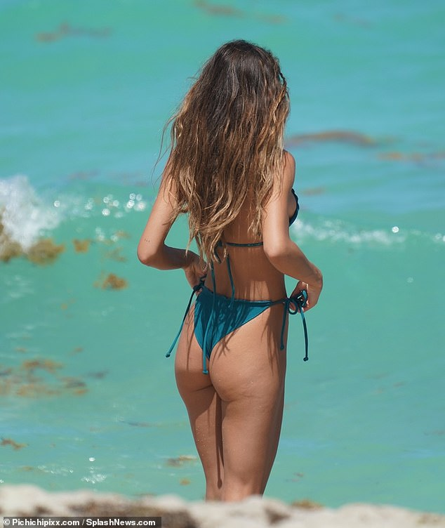 Sun day:The influencer rocked low-cut string green bikini bottoms, which showcased her per derriere and her sculpted midsection