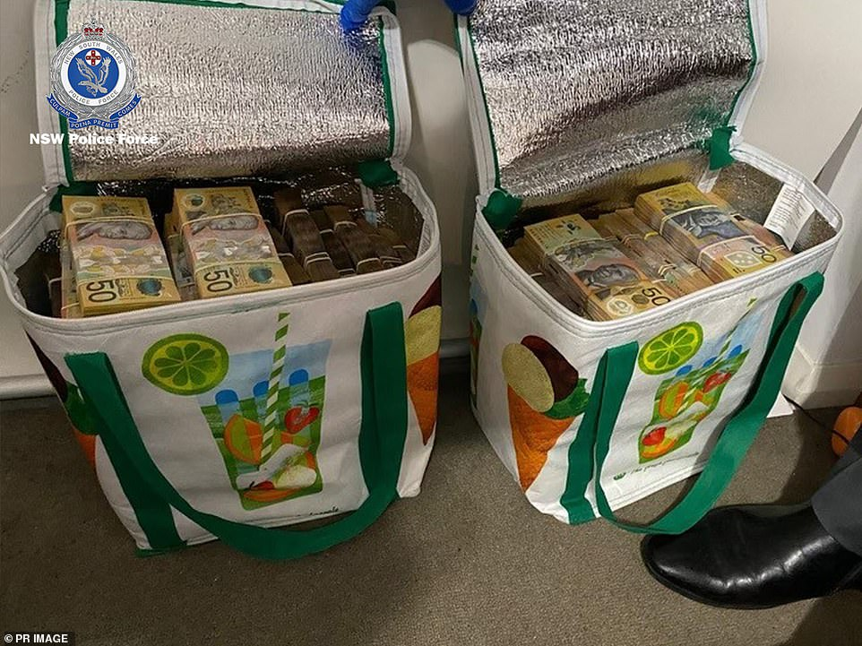 Picnic cooler bags are filled with stacks of cash which police in New South Wales seized on intelligence gained from the AN0M app