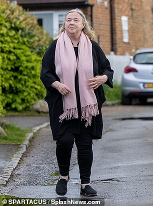 Sensible: She added a splash of colour by donning a pale pink scarf and completed her look by adding a pair of black shoes
