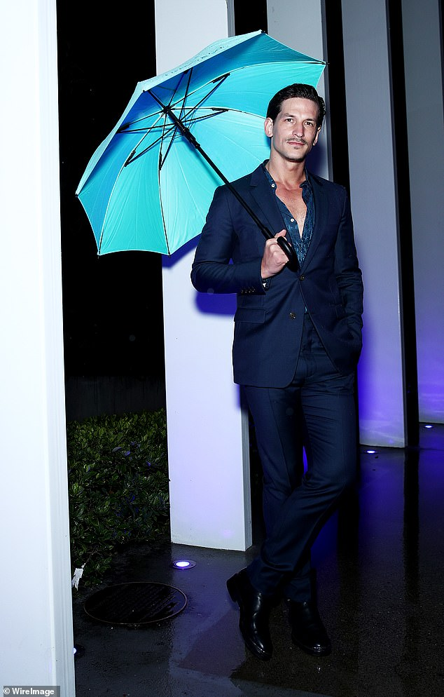 Working the camera: Also in attendance was Jarrod Scott, who put his model moves on display, posing with a blue umbrella