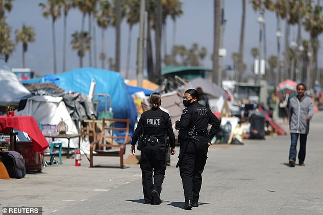 Police patrol the Venice Beach Boardwalk on April 20, which has seen an explosion in homeless numbers during COVID lockdowns