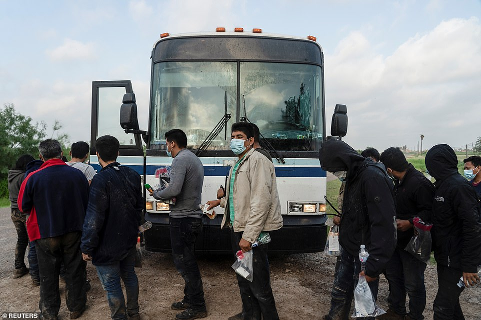 The migrants are transported on Tuesday by bus to holding facilities where they will be processed