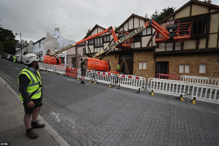 Construction: A worker keeps a careful watch as a local pub's facade is made-over for the upcoming film