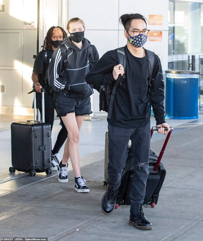 Leading the charge: 19-year-old Maddox is seen exiting the airport with his siblings close behind