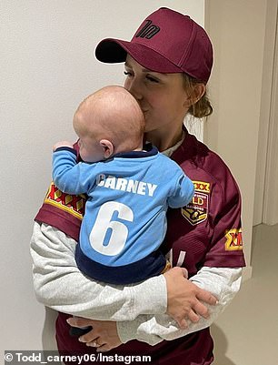 Divided: The former Cronulla Sharks star posted a photo showing his fiancée Susie Bradley wearing a maroon cap, in support of Queensland, as she carried their boy in his 'Carney' onesie