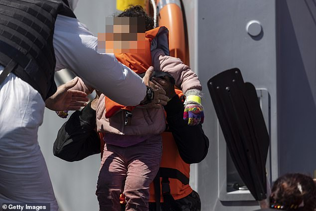 One official was seen holding a young girl who arrived in Dover yesterday