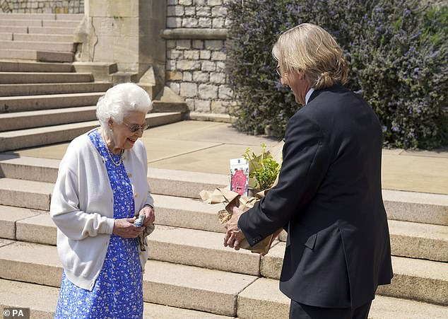 The Queen (pictured receiving the rose) has marked what would have been her beloved husband Prince Philip's 100th birthday on Thursday with a touching memorial at Windsor Castle