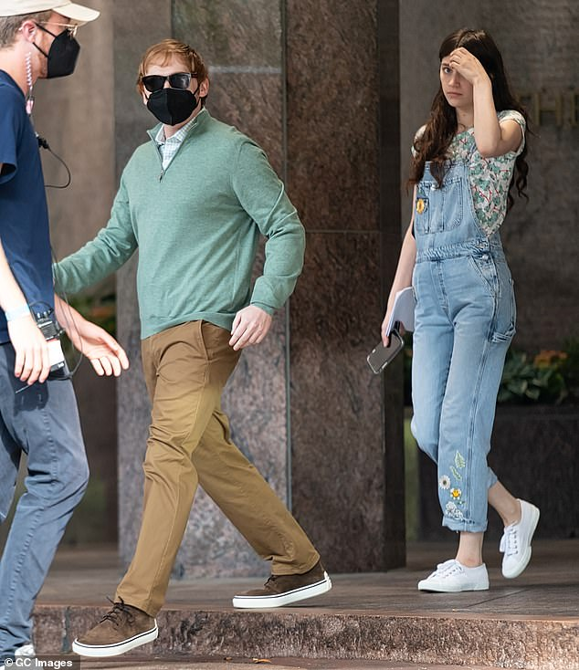 Taking a quick break: In between, she was seen holding a mobile phone while Rupert rocked a black face mask and discreet black shades
