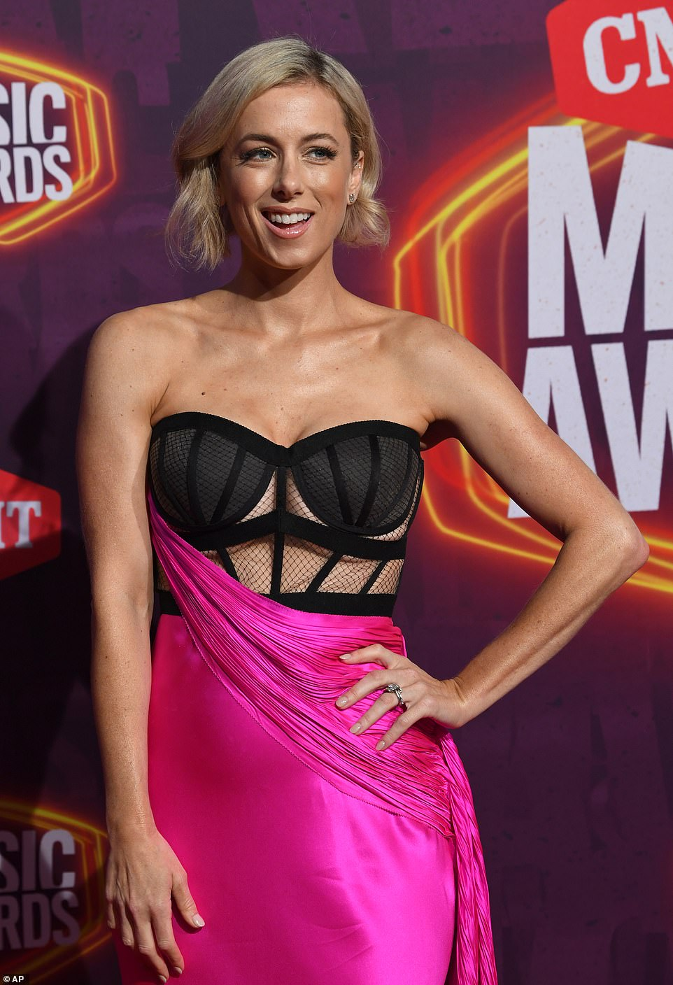 Mixed mediums:Taking a note from Kelsea's book, comedian Iliza Shlesinger slipped her toned physique into a hot pink satin gown with a sexy mesh bodice