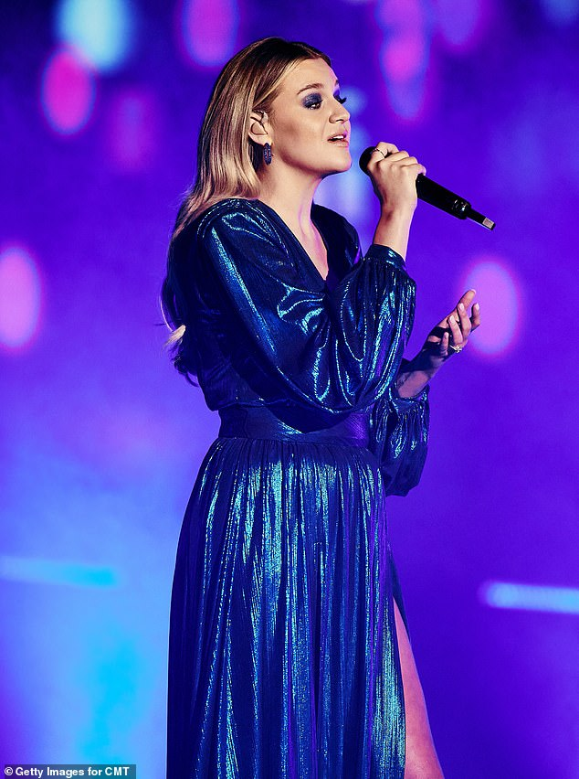 Bringing the drama:For her stunning performance with Paul Klein, the singer-songwriter modeled a metallic teal gown with a dramatic leg slit