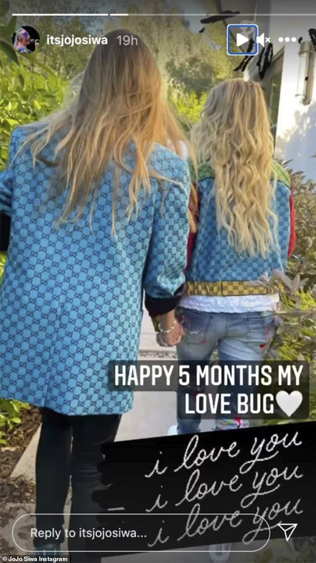 Love bug:Siwa also shared another snap of the couple walking together from behind, hand-in-hand, with Siwa adding, 'Happy 5 months my love bug,' with 'I love you' written thrice in cursive