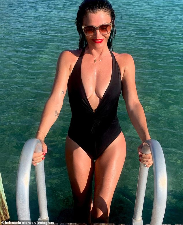 Wow! Helena Christensen, 52, flaunted her incredible figure in a plunging black swimsuit as she emerged from a swimming pool in a collection of Instagram snaps on Thursday