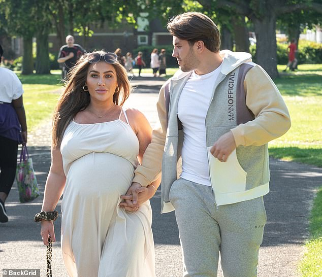 Beautiful:Lauren gentle cradled her growing bump as she enjoyed a stroll in the warm weather dressed in the flowing white dress
