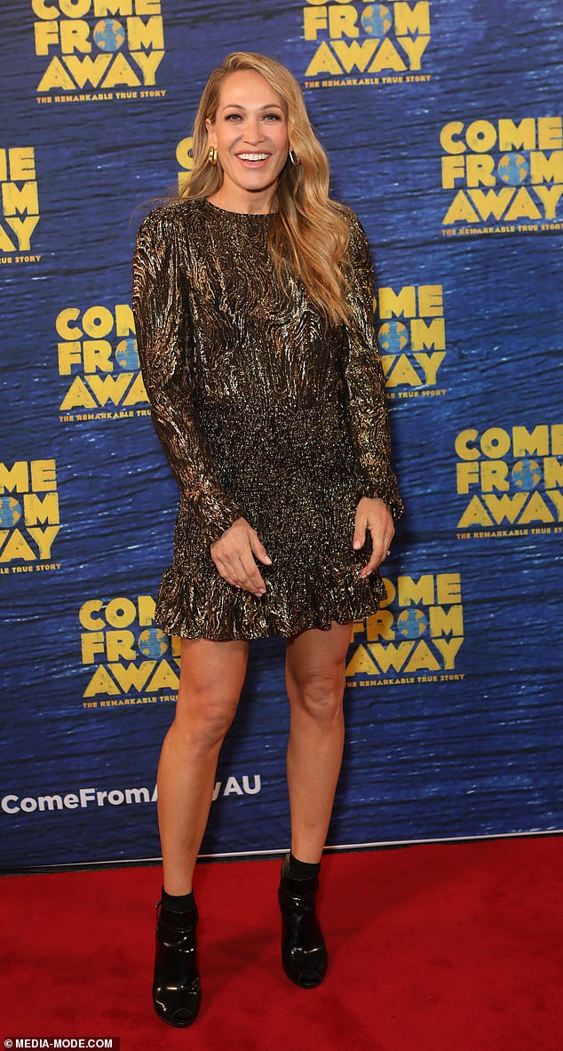 Heavy metal: Erika Heynatz looked stylish in a sparkly gold and black patterned mini-dress with puff sleeves and a shirred waist