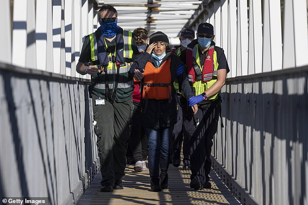 Border Force officials guide a pregnant lady ahead of other newly arrived migrants to a holding facility after being picked up in a dinghy in the English Channel yesterday morning