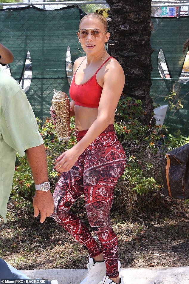 She must work out: Lopez's muscular biceps were on display as she sported a strappy red bra top with a thick band around her back