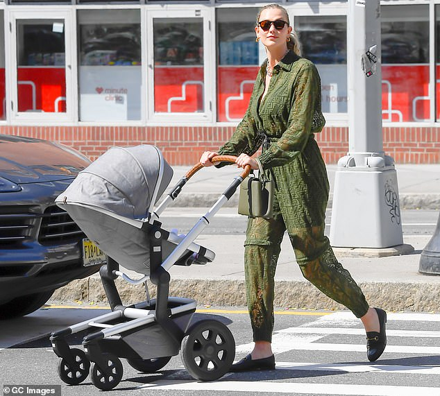 Dressing well: The former Victoria's Secret Angel wore a stylish green Fendi jumpsuit while spending time with her newborn child