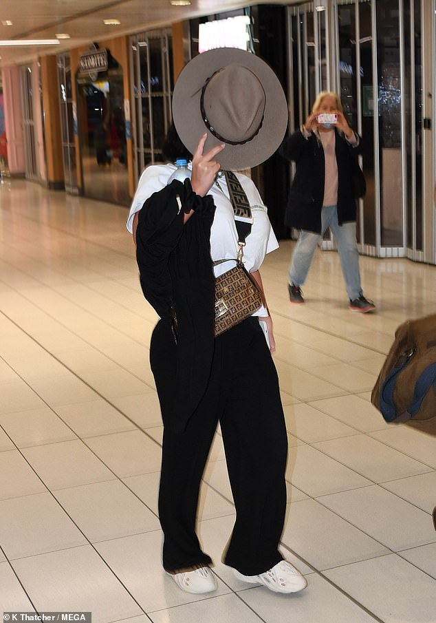 Hiding: On Thursday MAFS and Celebrity Apprentice star Martha Kalifatidis oddly covered her face and hid AGAIN from paps as she landed in Sydney with boyfriend Michael Brunelli