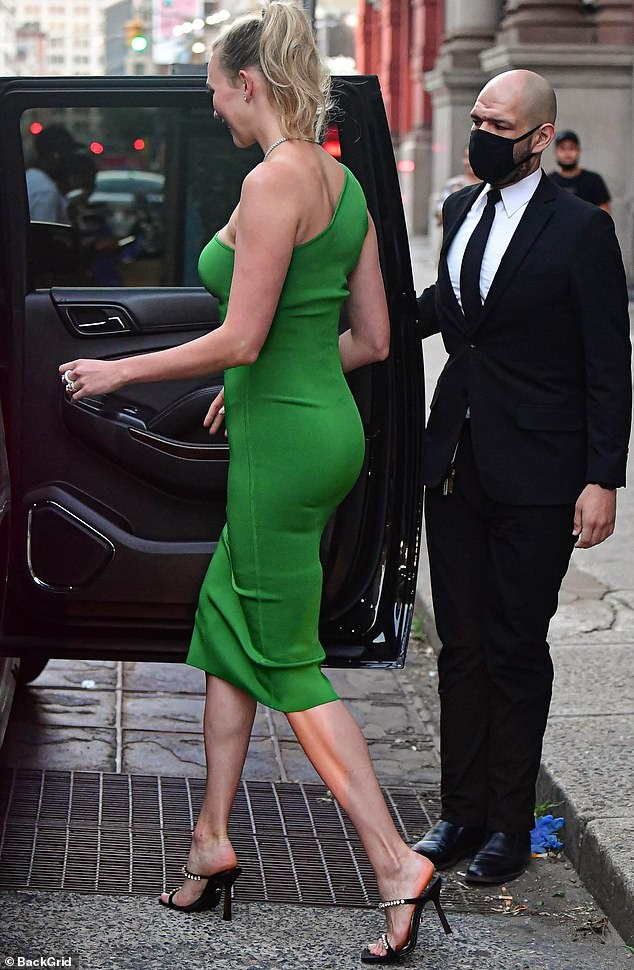 Mover and shaker: Karlie, who shares her son Levi Joseph with her husband Joshua Kushner, was seen heading towards a black SUV whose door was opened by a man in a bright suit