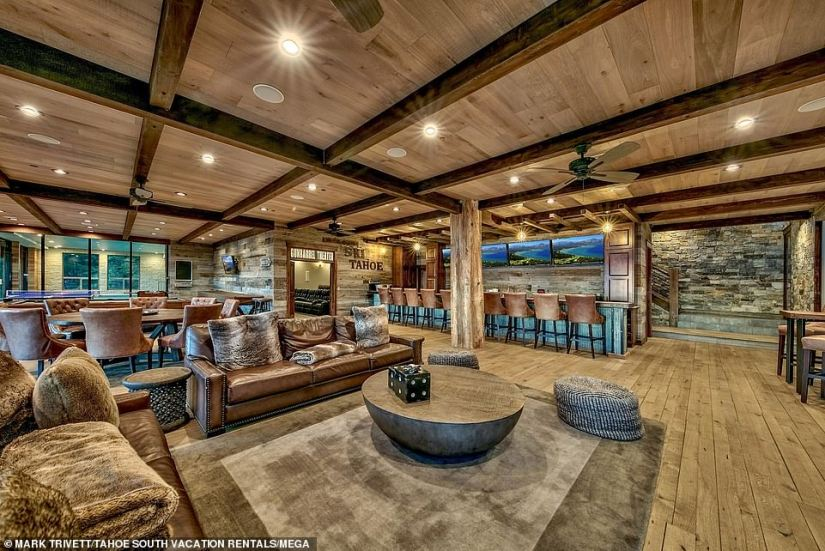 Opulent: The woodsy home includes a large living room area with couches and a table