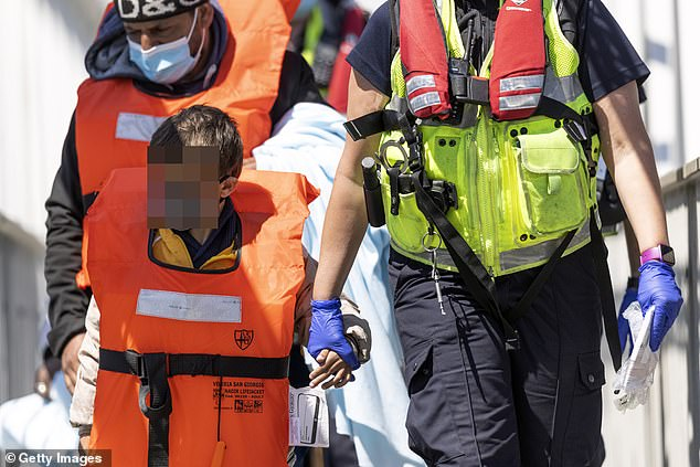 An official guided newly arrived migrants to a holding facility after they were picked up in a dinghy