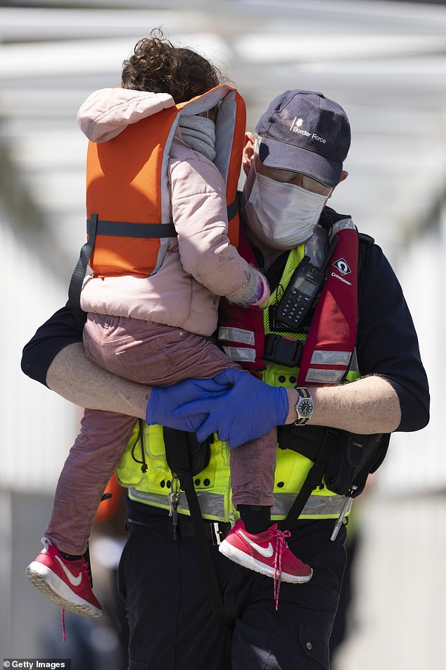 A Border Force official holds a young girl that arrived with other migrants after they were picked up in a dinghy yesterday