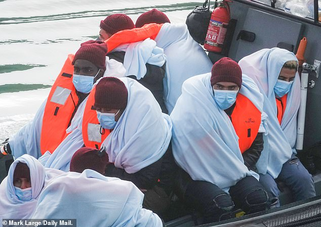 The intercepted migrants huddle in a boat as they are taken to the shore yesterday in Kent