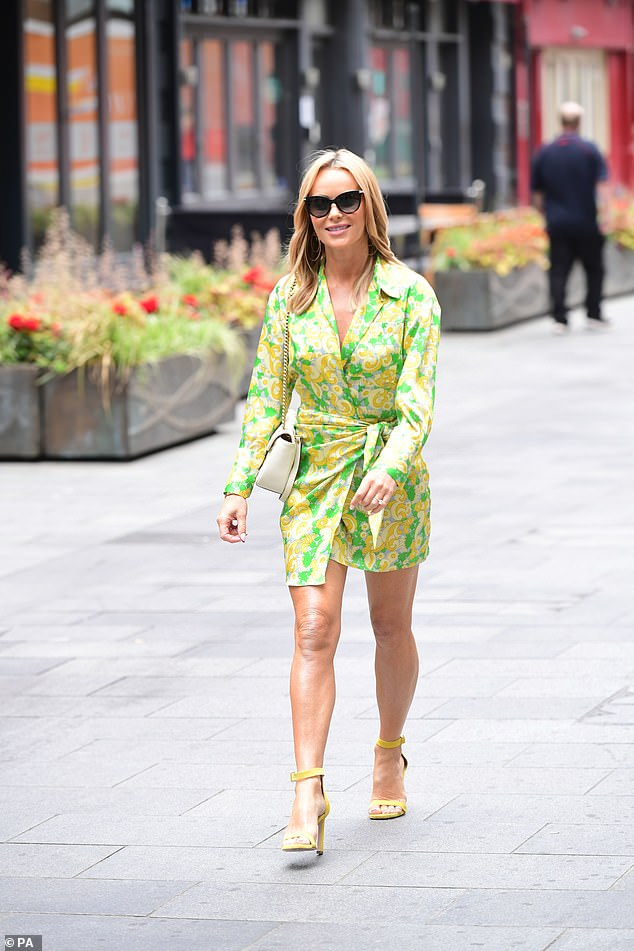 Here comes the sun: Amanda's stylish floral-patterned dress was cinched in at the waist to give her an hourglass figure