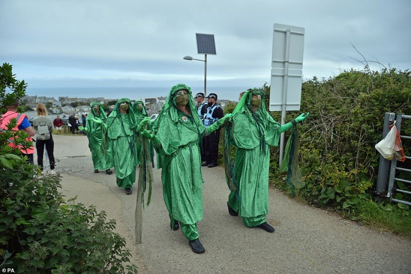People dressed in green hold their hands up as they lead the procession out of the leisure centre in St Ives