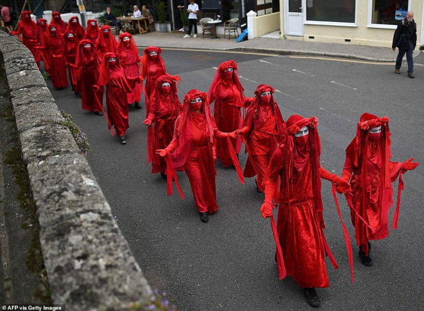 The protesters held up their hands as they donned red outfits and white face paint for maximum effect