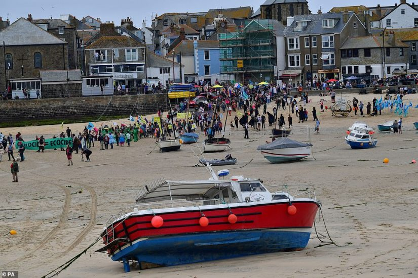 Boats can be seen on the beach, left by fisherman, as the march passes them in St Ives