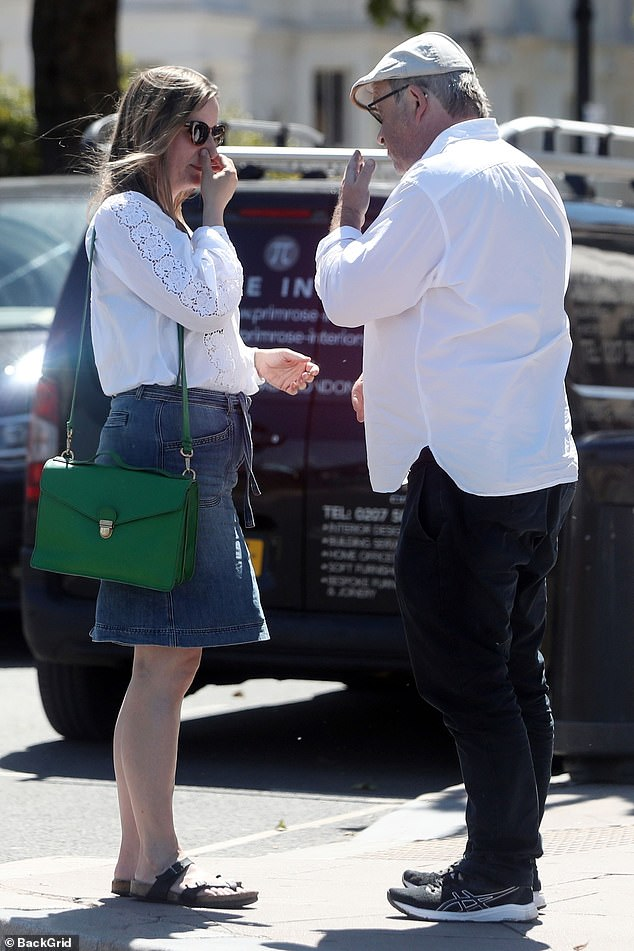 Style: Meanwhile, Catherin looked chic and casual in a white blouse, denim skirt, and sandals while carrying a bright green leather handbag