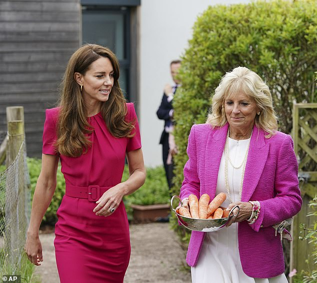 Kate, Duchess of Cambridge, left, and US First Lady Jill Biden, carrying carrots for the school rabbit, Storm