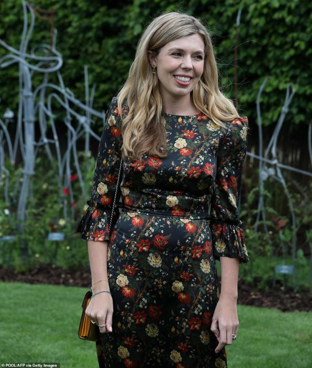 Carrie wore a subdued black floral dress in contrast with the fuchsia pink number she donned to meet leaders earlier today