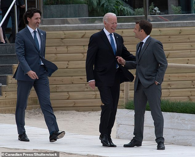 President Joe Biden (center) laughs as he speaks with French President Emmanuel Macron (right) and Canadian Prime Minister Justin Trudeau