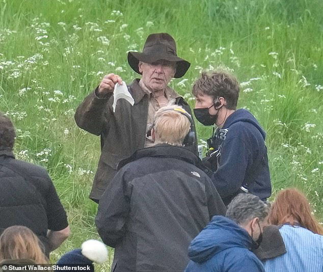 Look what I found: Harrison was also seen handing a cleaning wipe he had found in the grass to a member of staff