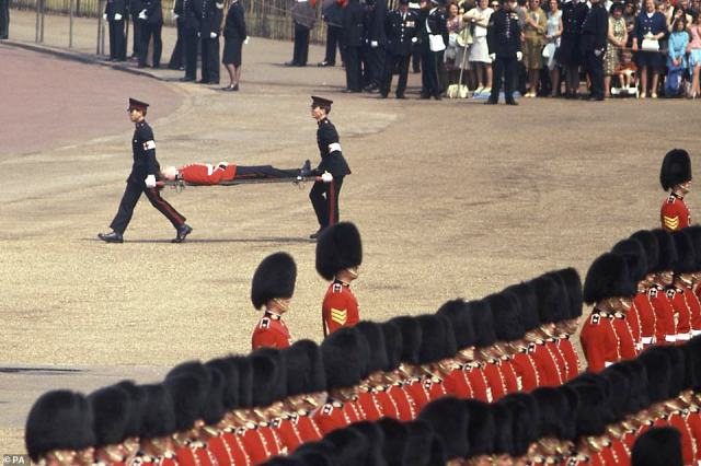 1969 — A FAINTING GUARDSMAN: In 1969, an unconscious Guardsman was carried off as The Queen inspected the 1st Battalion, the Scots Guards, on Horse Guards Parade to mark the official birthday of The Queen. Fainting guards during Trooping the Color have become something of a tradition at the yearly event: Temperatures frequently soar, and despite hours of training, the heat sometimes overwhelms them.
