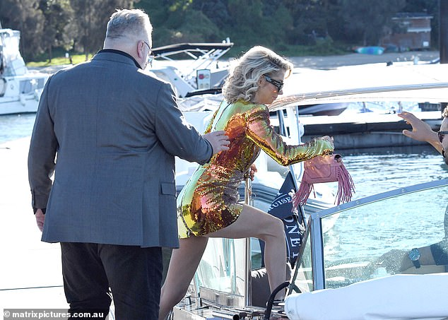 The couple's speed boat had arrived and was ready to take them to the party. Kyle helped Tegan on board as shetook a large stride to get on