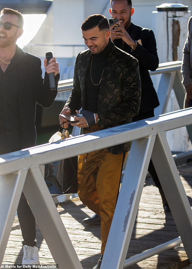 Gifts: He carried a black gift bag with a card that read: 'To Kyle (heart) Guy' as he followed Kyle's security personnel down the wharf