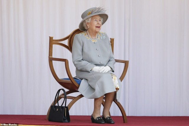 The Queen smiled during the ceremony as she perched while the Household Division performed at Windsor Castle