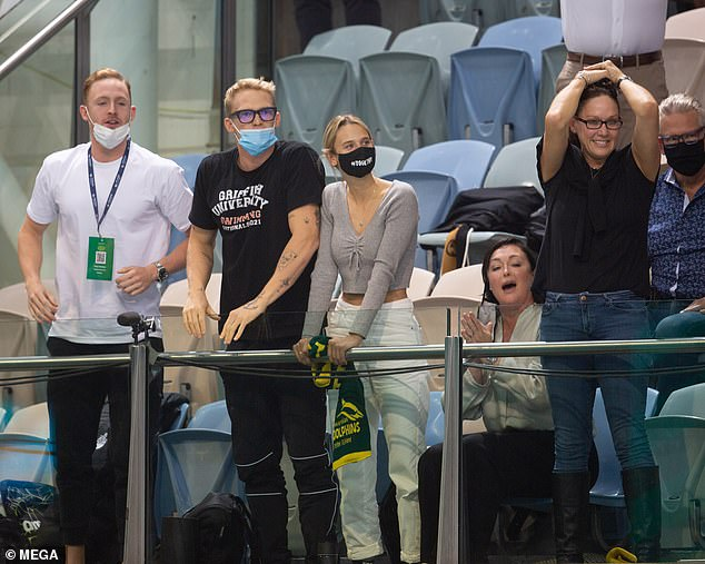 Cheering them on: The 24-year-old cut a relaxed figure in black jeans and a color-matched t-shirt as he watched other swimmers compete with his girlfriend Marloes and mother Angie