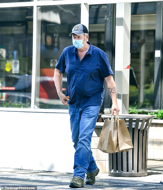 Casual Saturday:The country star, 44, sported his trademark casual style on the outing, in a blue button-down shirt and light wash denim jeans