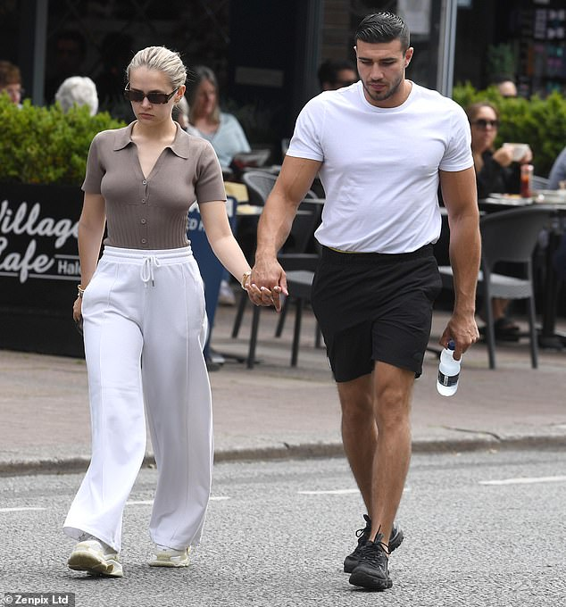 Muscles:Holding his girlfriend's hand, Tommy showcased his muscular build in a fitted white T-shirt and made the most of the warm weather in a pair of black shorts
