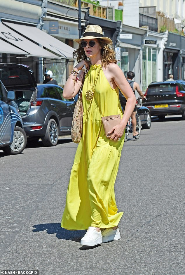 Looking fab:Trinny Woodhall, 57, looked simply fabulous on Sunday when she stepped out for a spot of shopping in Notting Hill wearing a bright yellow dress