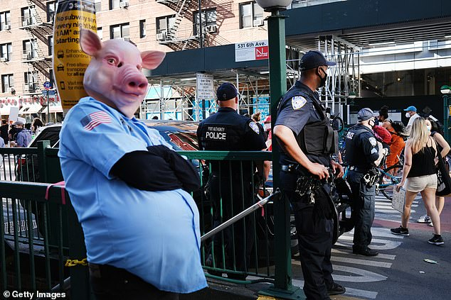 A man in a costume watches as protesters march on June 16, 2020 in New York City
